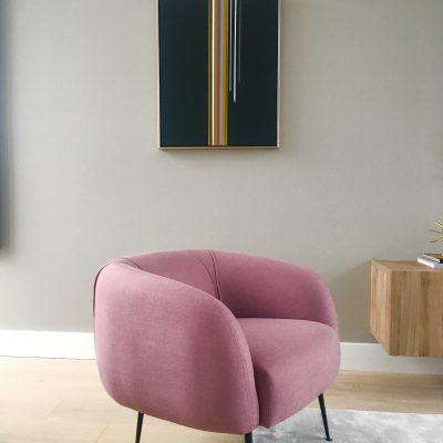 Artwork behind accent chair, a focal point when entering room