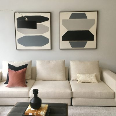 Artwork complements accent wall color, sofa, pillows and sculptures - interior design by Urban Casa