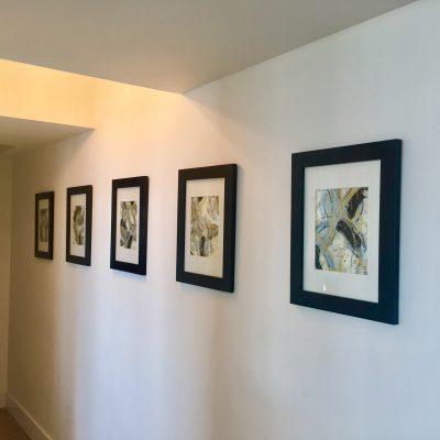 Hallway wall displaying 5 matching framed art pieces